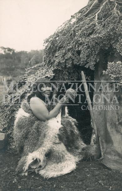 Donna Selknam (Ona) davanti alla capanna Argentina, Patagonia, Terra del Fuoco, Isola Grande  (1915 ca.) Gelatina bromuro d'argento : carta, 139 x 89